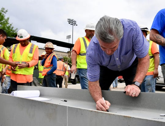 Dan Radakovich, Clemson University Athletics Director, signs the last beam to go up at the construction site for a softball stadium at Clemson University during the softball topping out ceremony in Clemson Tuesday.
