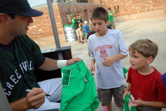 A player signs a Green Day t-shirt.