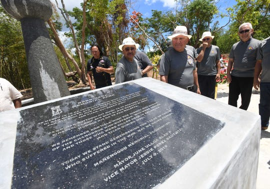 World War II survivors and others read the inscription engraved on a stone plaque after it was unveilled during the dedication of the Kålaguak Memorial in Tiyan, Barrigada on Tuesday, July 9, 2019. The memorial was established to remember those who died in the area during the dark times of World War II, especially the CHamoru people who were forced to manually build an airstrip in the area, under the rule of occupational Japanese forces.