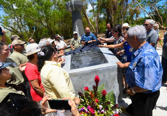 World War II survivors and others gather around an engraved stone plaque as it is unveiled during the dedication of the Kålaguak Memorial in Tiyan, Barrigada on Tuesday, July 9, 2019. The memorial was established to remember those who died in the area during the dark times of World War II, especially the CHamoru people who were forced to manually build an airstrip in the area, under the rule of occupational Japanese forces.