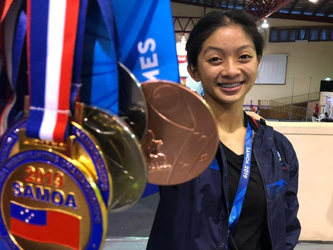 Dayamaya Calma with her medal haul after her Pacific Games weightlifting debut in Samoa July 9. Calma, 17, took silver medals in the snatch and total weight, as well as a bronze medal in the clean and jerk in the 49kg weight class.