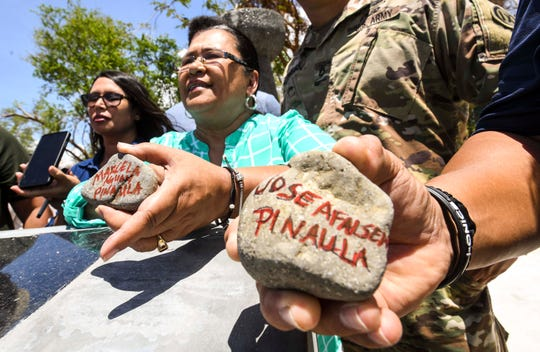 Barrigada resident Mary Pinaula Cruz and other family members show stones marked with names of loved ones before being added to a water fountain during the dedication of the Kålaguak Memorial in Tiyan, Barrigada on Tuesday, July 9, 2019.