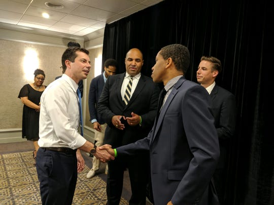 Kevin Johnson (center) watches as Pete Buttigieg shakes hands with Khariell Pinkney at a fundraiser July 2 in Chicago.