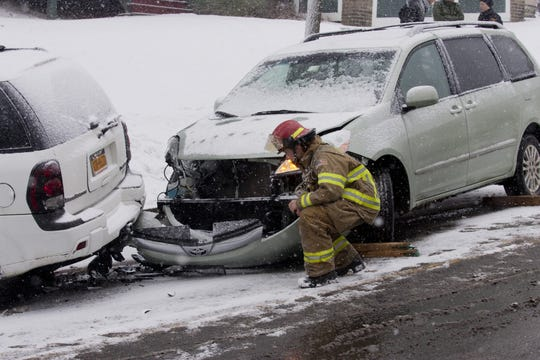 Firefighter Daryl Pace inspects damage to a vehicle involved in a minor accident on Aurora Street in Ithaca in January 2015.