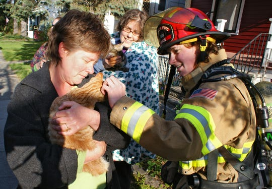 Michele Hochstetter, left, holds her cat Mango, and Marriah Prentiss, center, holds their other cat Ripple as Ithaca Firefighter Daryl Pace visits after a fire in their home in April 2012. Pace and Firefigther Jared Gebel found the cats after the smoky fire.