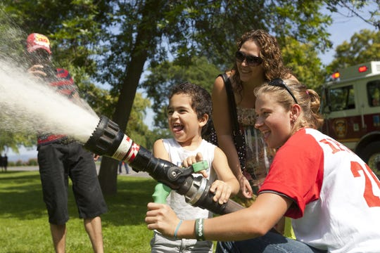 Ithaca firefighter Daryl Pace, right, helps 3-year old Nathaniel Alvarez, of Ithaca, work a fire hose while his mother, Alesha, looks on during the 20th annual Ithaca Professional Firefighters Association Kids Day at Stewart Park in August 2013.