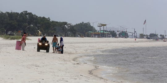 In this June 25, 2019 photo, a Harrison County Sheriff's deputy rides along the sand warning beach-goers to stay out of the water in Long Beach, Miss. Toxic bacteria are keeping swimmers out of the water on the Mississippi Gulf Coast, and it will be weeks before financial information shows whether beach closures are hurting the local economy. The state is warning people and pets to stay out of the water because of pollution coming from the Mississippi River and spreading eastward.