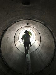 A researcher hikes through a storm water culvert that allows Sandy Creek to flow under a roadway.