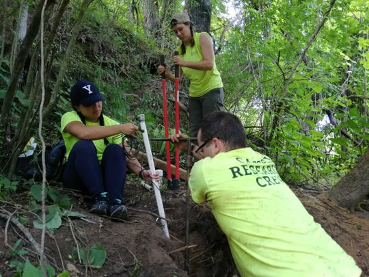 Researchers remove a soil moisture probe that helps determine how rainfall moves through the soil into the aquifer.