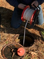 Researchers take a water level measurement in a monitoring well in Fayette County – part of the recharge zone of the Memphis aquifer.