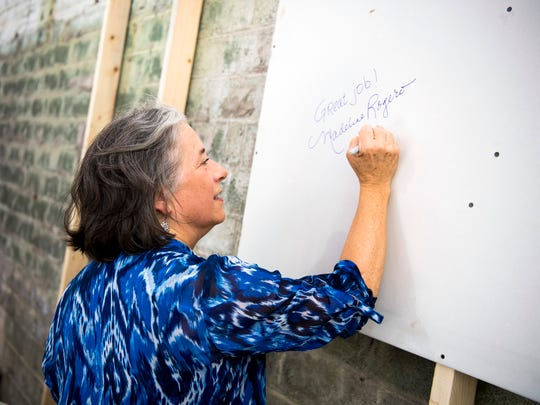 Knoxville Mayor Madeline Rogero writes a message onto Sheetrock at South High in Knoxville on Tuesday, July 9, 2019. South High is being redeveloped into a senior living center.