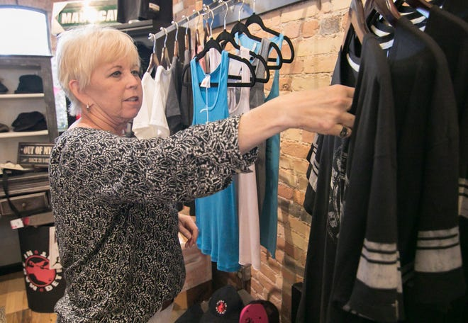 EnCore 118 Custom Furnishings and Boutique store co-owner Cathy Bateman adjusts 'Made in Detroit' products Tuesday, July 9, 2019.  The downtown Howell store recently closed.