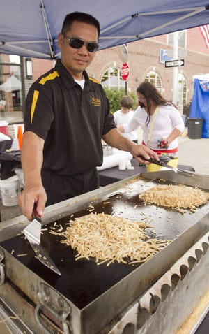 Sagano Japanese Bistro & Steakhouse chef Matthieu Nguyen prepares noodles and chicken fried rice at the 2016 A Taste of Brighton. This year's festival runs Friday and Saturday downtown.