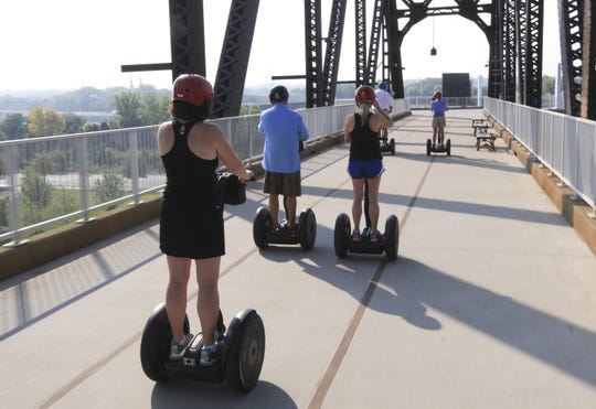 The Segway tour group rolls back across the Big Four pedestrian bridge.
