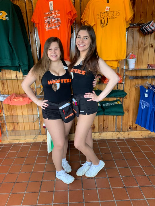 Madilynn Mills, left, and Paige Chaffin are servers at the Hooters restaurant in Lansing. The restaurant is expected to close Saturday after 18 years of business.
