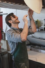 Miles Tamboli hand tosses pizza dough in his new restaurant Tamboli Pasta & Pizza. The new Midtown Memphis dining spot is slated to open in September.