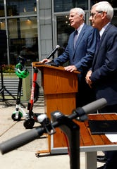 Milwaukee Mayor Tom Barrett, left, is joined by Wisconsin Gov. Tony Evers on Monday at the Milwaukee Public Market for the signing of a bill allowing local governments to regulate electric scooters.