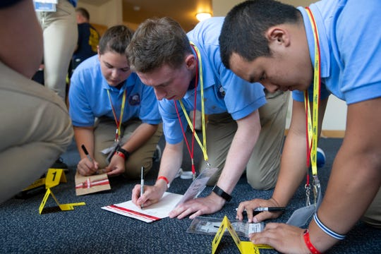 Sara Lesniewski (from left), Bradley Moren and Andrew Lee learn how to file evidence they collected from the staged crime scene during the Future Law Enforcement Youth Academy in Humphrey Hall at Marquette University on Tuesday, July 9, 2019. The youth academy accepted students from across the state to go through a weeklong integrated scenario simulation where they learn the stages of solving a crime.