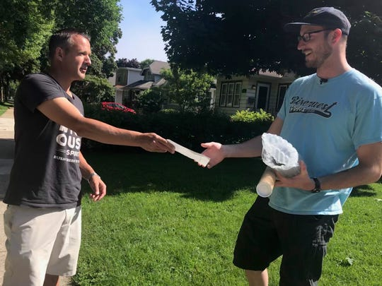 Rush Creek Distillery co-founder Todd Stricker hands a check for $1,000 to Henry Sanders, who plans to take a nearly two-month road trip from Prague to Russia.