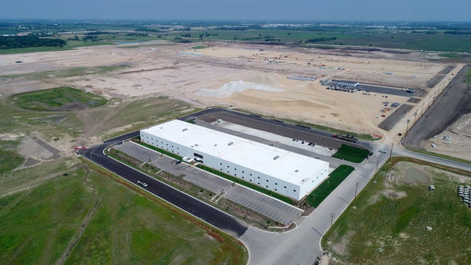 A multipurpose building (front) is up and a display-panel factory that will include multiple buildings is under construction on a pad of crushed, compacted gravel at Foxconn Technology Group's planned manufacturing complex Tuesday in Mount Pleasant.