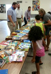 Twin Lakes Future Fund members Bailey Bodenhamer (from left), Eric Lunnen and Philip Frame delivered books to children partcipating in the Seamless Summer Feeding Program at Norfork Public Schools.