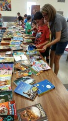 Courtney Wilson, facilitator of the K-6 program, helps a child view books on Monday at Norfork Public Schools.