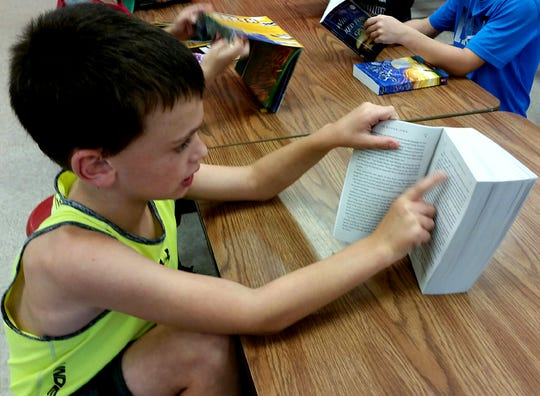 A child follows the lines of the page as he reads Harry Potter on Monday at Norfork Public Schools.