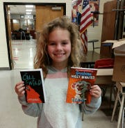Jazzalyn Jones shows off the books she chose on Monday at Norfork Public Schools.