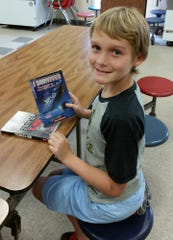 Jeremy Jones shows off the books he chose from the boxes of books donated the Twin Lakes Future Fund on Monday.