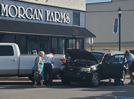 Country music star Craig Morgan squats (behind car door) looking for snake. Morgan owns Morgan Farms store, pictured in background.