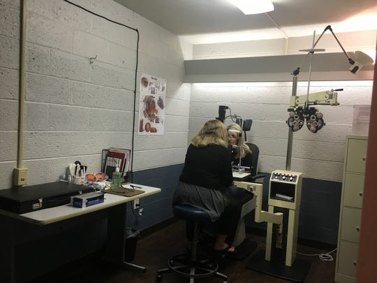 Optometrist Kathy Wise poses a mock vision exam on Lori Hubble, Director of the Look Up Center, during an interview at the Look Up Center in Newark.