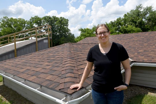 Sarah Jones, a senior engineer for Owens Corning in the Process and Materials Innovation Group in the Roofing Division, by the shingle decks built for field testing shingles at the Science and Technology Center in Granville.