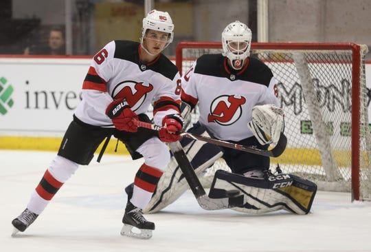 Jack Hughes tips the puck to try and get it past goalie Cole Brady as they work out with other young players in the Devil's organization at their 2019 Development Camp held at the Devils practice facility in Newark.