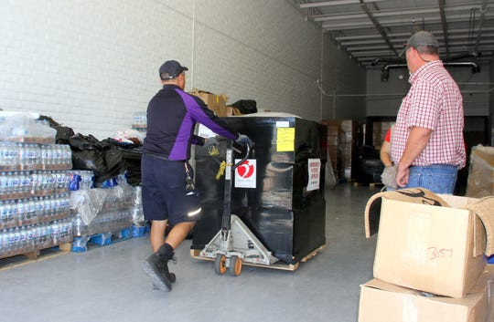 City Administrator Aaron Sera looks on as a FedEx courier delivers supplies to the Deming Migrant Relief facility (National Guard Armory).