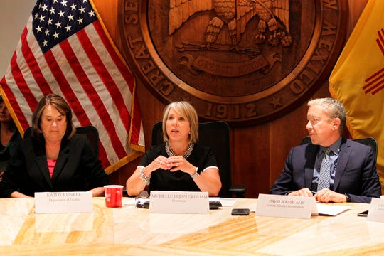 New Mexico Gov. Michelle Lujan Grisham, center, flanked by members of her cabinet, provides a progress report on her first six months in office during a news conference in Santa Fe, New Mexico, on Tuesday, July 9, 2019.