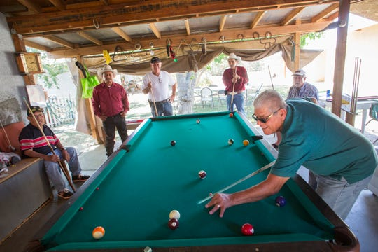 Alfonso Diaz plays billiards at the home of Don Jesus Espinoza, whom put up his house so his friends could play billiards after they were no longer able to do so at the Indio Senior Center.