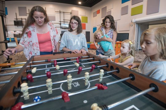 Branches of Hope (single mothers group) members Joni Verlin, left, and Jaclyn Smith, top right, play foosball with their children at Olive Baptist Church in Pensacola on Monday, July 8, 2019.  Olive Baptist Church will be hosting a Single Moms Conference this weekend.