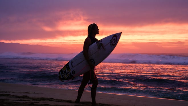 "Professional surfer Bethany Hamilton walks along the beach, surfboard in hand, in the documentary ""Bethany Hamilton: Unstoppable."""