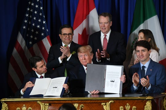 U.S. President Donald Trump signs the United States-Mexico-Canada trade agreement with Canadian Prime Minister Justin Trudeau  and former Mexican President Enrique Pena Nieto at the G-20 summit in November 2018.