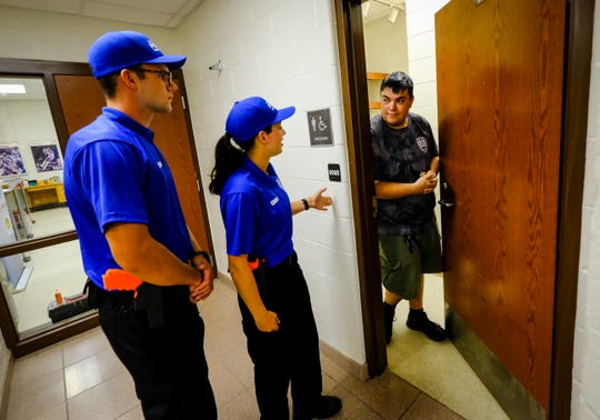 Port Huron Police Cadet Dean Peacock, right, answers the door for students Aaron Smith, left, and Allison Groff, who are responding to a call during a domestic violence simulation Monday, July 8, 2019, at the Port Huron Police Youth Academy, held at Port Huron Northern.