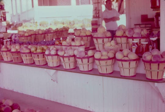 Peaches on display in roadstand facing S. George St. My mother's cousin, Larry Miller, is in background.