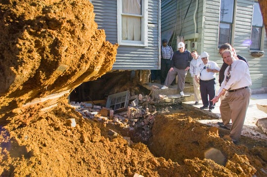 In this file photo, officials survey an excavated sinkhole in the front of 482 West Philadelphia Street in York after the sidewalk was pulled away to see how far into the sidewalk it had extended.