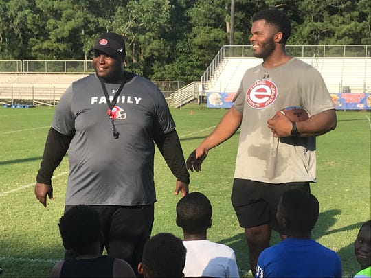 Evangel coach Byron Dawson and L.A. Chargers lineman Jerry Tillery share a laugh Monday during the inaugural Jerry Tillery Championship Football Camp at Evangel.