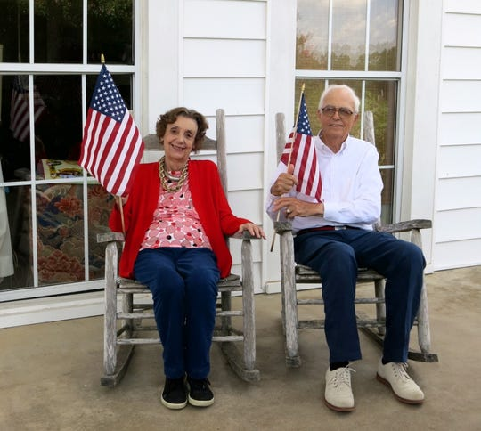 Hosts Garland and John Guth were hosts for the July 2 Lunch at Fairview Farm. With flags in hand, they pose on the porch of the house.