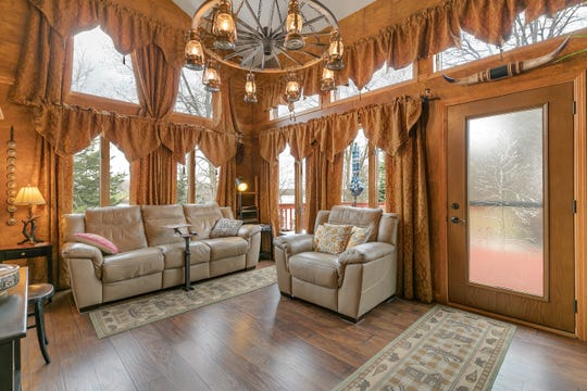 The living room has a high vaulted ceiling with two stories of windows and a chandelier.