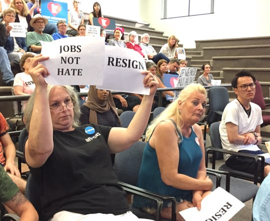 Jane Conrad of the East Central Area Labor Council holds up signs Monday, July 8, 2019, asking St. Cloud City Council members Paul Brandmire and Mike Conway to resign following a New York Times story about the C-Cubed group that Brandmire and Conway were sympathetic to during their election campaigns.