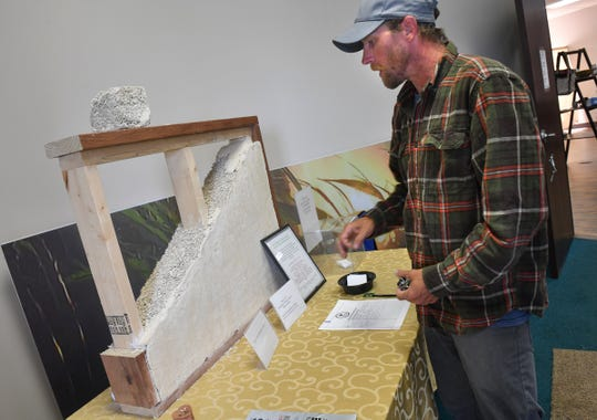 Justin Trott talks about a display showing hemp-based building materials and insulation Tuesday, July 9, 2019, at 419 Hemp in St. Cloud.