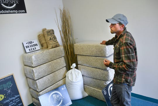 Justin Trott talks about the many types of cannabis products, including material used as mulch or animal bedding, available Tuesday, July 9, 2019, at 419 Hemp in St. Cloud.