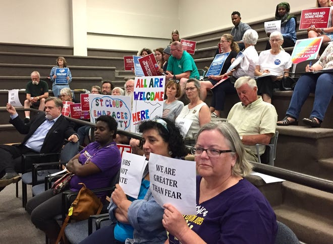 "Community members at the St. Cloud City Council meeting on Monday, July 8, 2019, hold up signs that state, ""All are welcome here"" and ""We are greater than fear."""