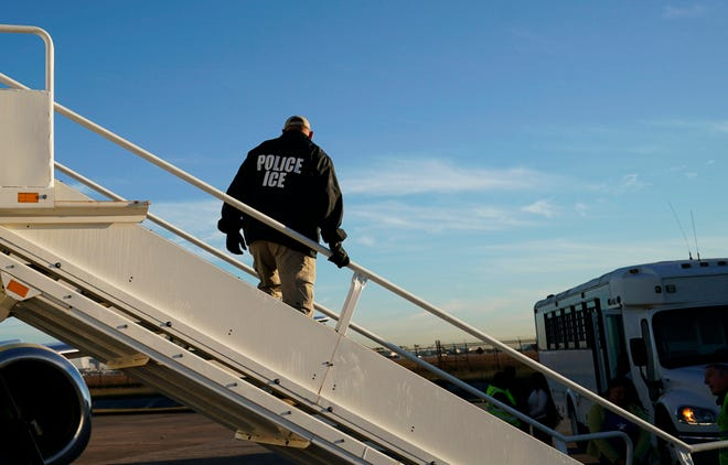 In this Nov. 16, 2018, file photo, an officer watches as immigrants who entered the United States illegally are deported on a flight to El Salvador by U.S. Immigration and Customs Enforcement in Houston. Civil rights activists complained Monday of the potential for widespread abuse following confirmation that states have scanned millions of driver's license photos on behalf of Immigration and Customs Enforcement officials without knowledge or consent.